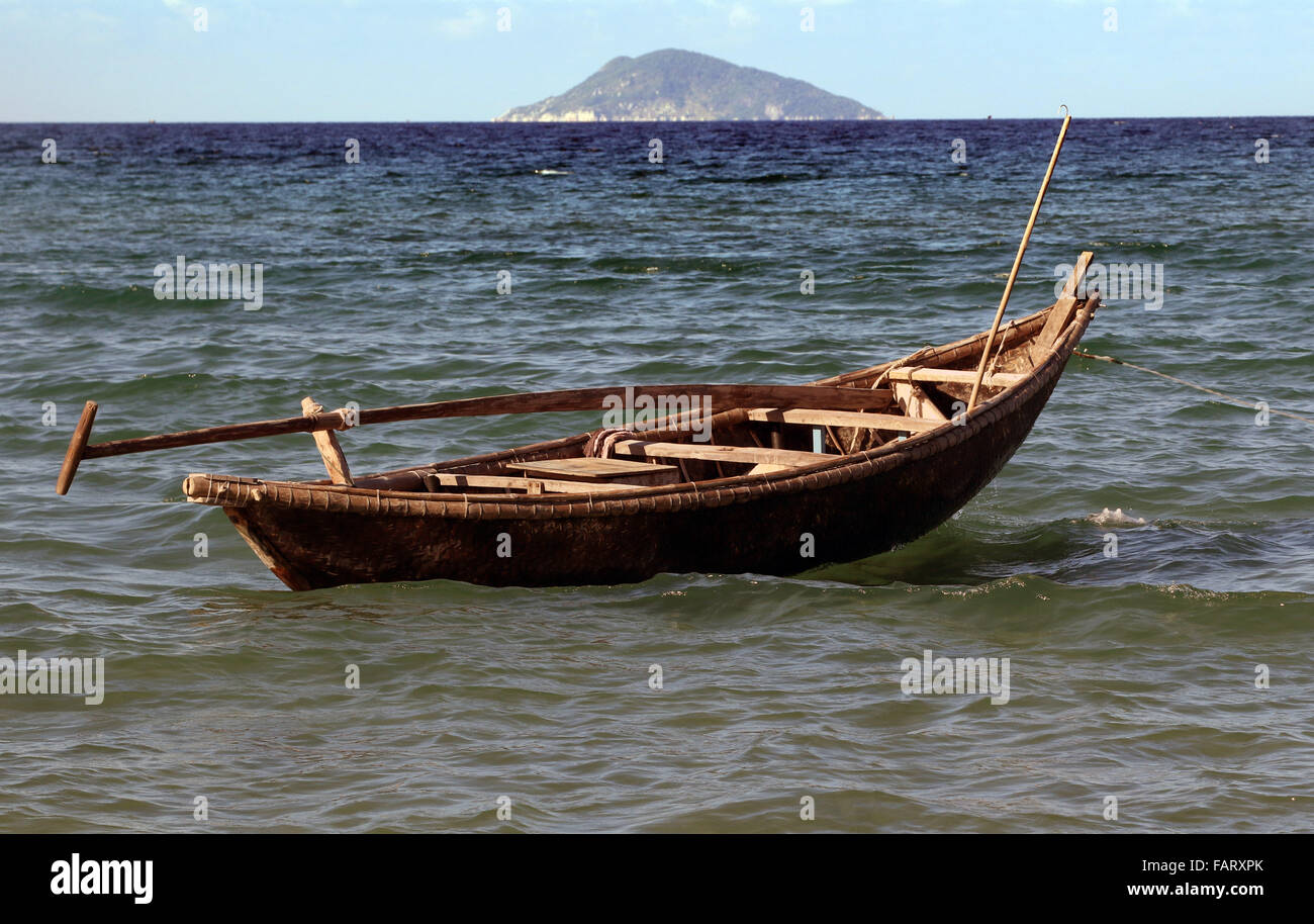 South China Sea traditional boat floating off beach - Stock Image
