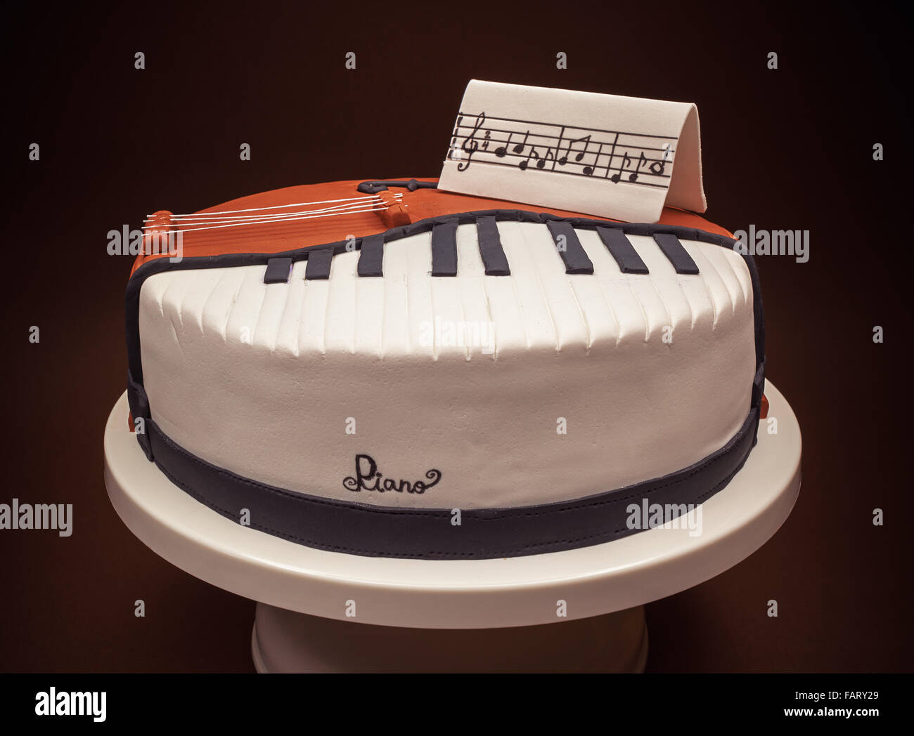 Birthday cake decorated with fondant, rounded, symbolically presenting piano and cello instruments. - Stock Image