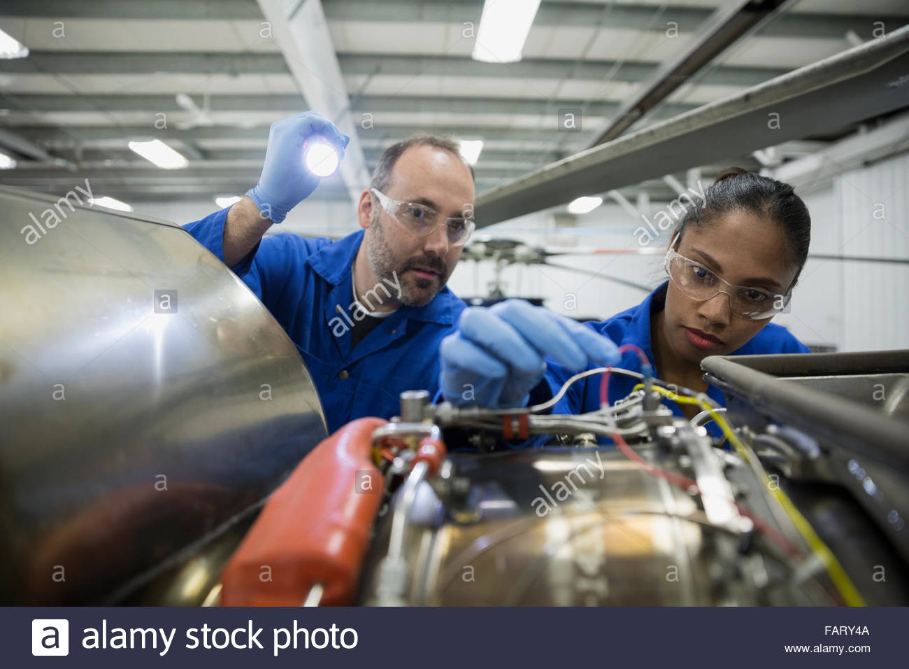 Helicopter mechanics working on part with flashlight - Stock Image