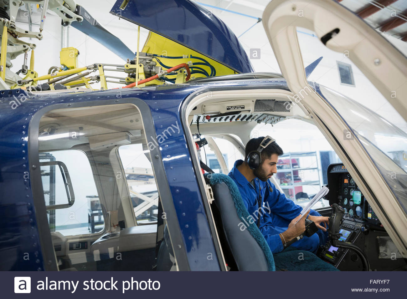 Mechanic checking instruments in helicopter cockpit - Stock Image