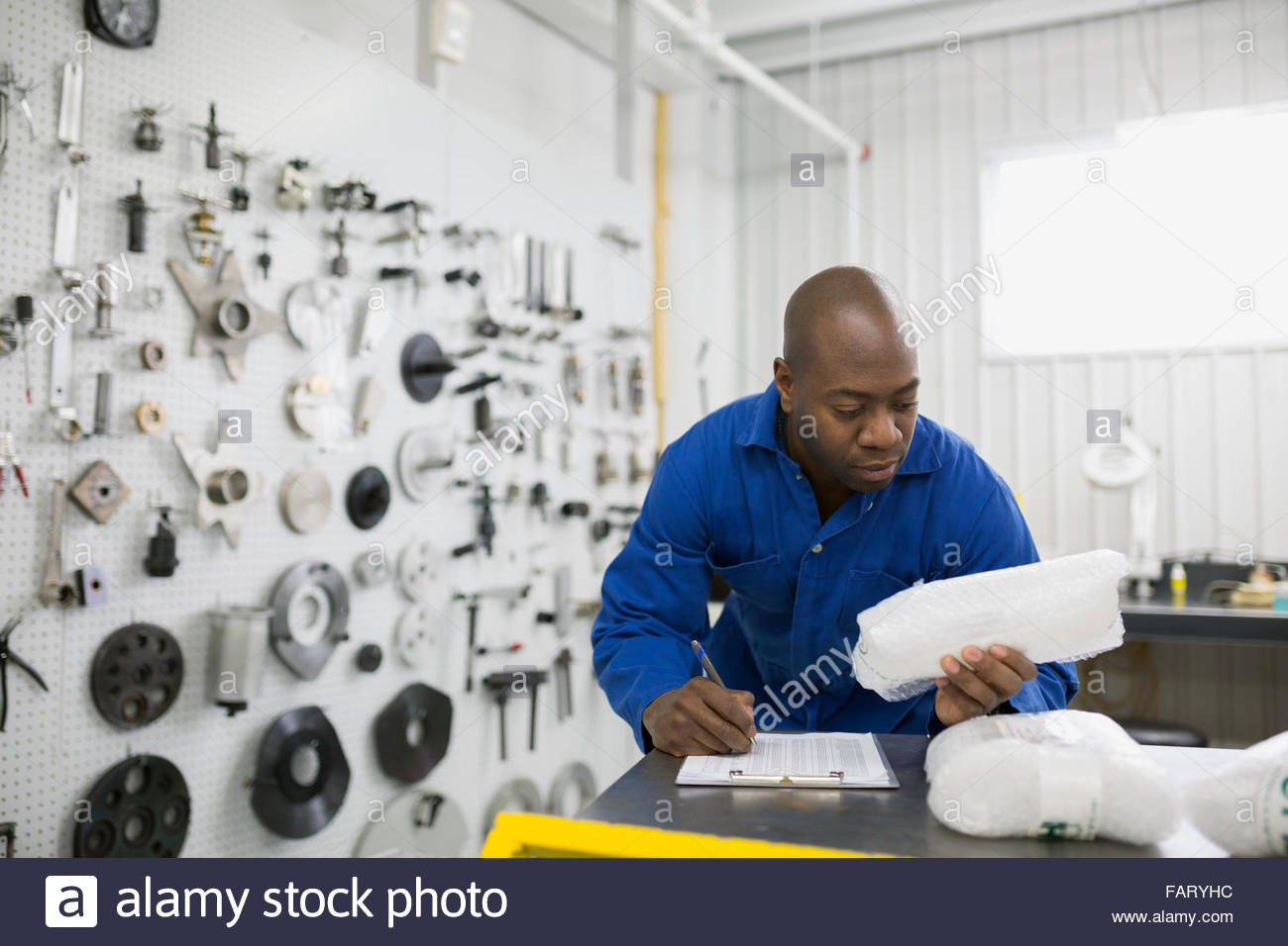 Helicopter mechanic with clipboard examining part - Stock Image