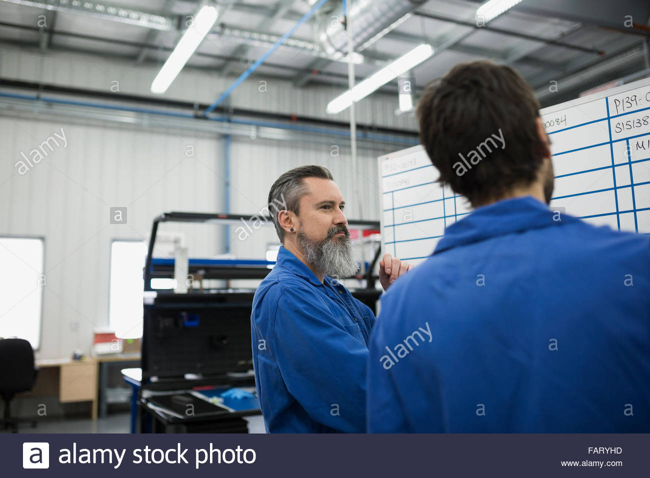 Helicopter mechanics planning at whiteboard - Stock Image
