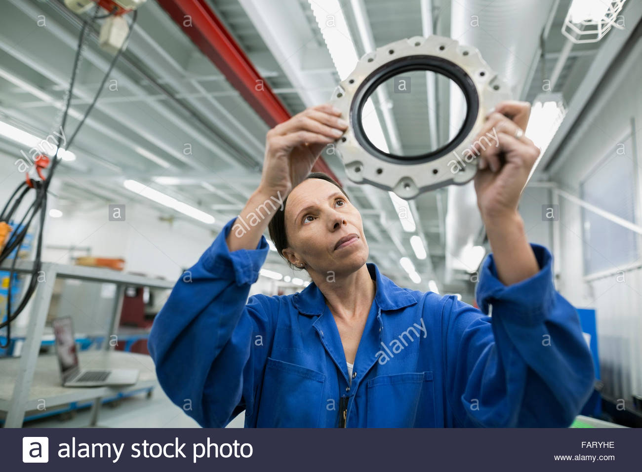 Female helicopter mechanic examining disc in airplane hangar - Stock Image