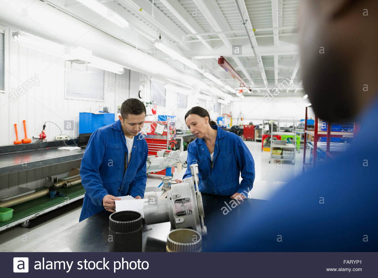 Helicopter mechanics examining parts in workshop - Stock Image