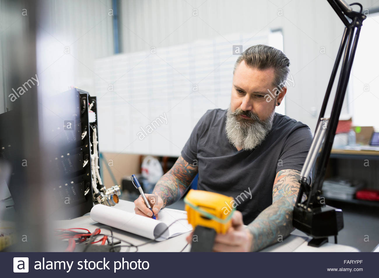Helicopter technician performing diagnostics on module - Stock Image