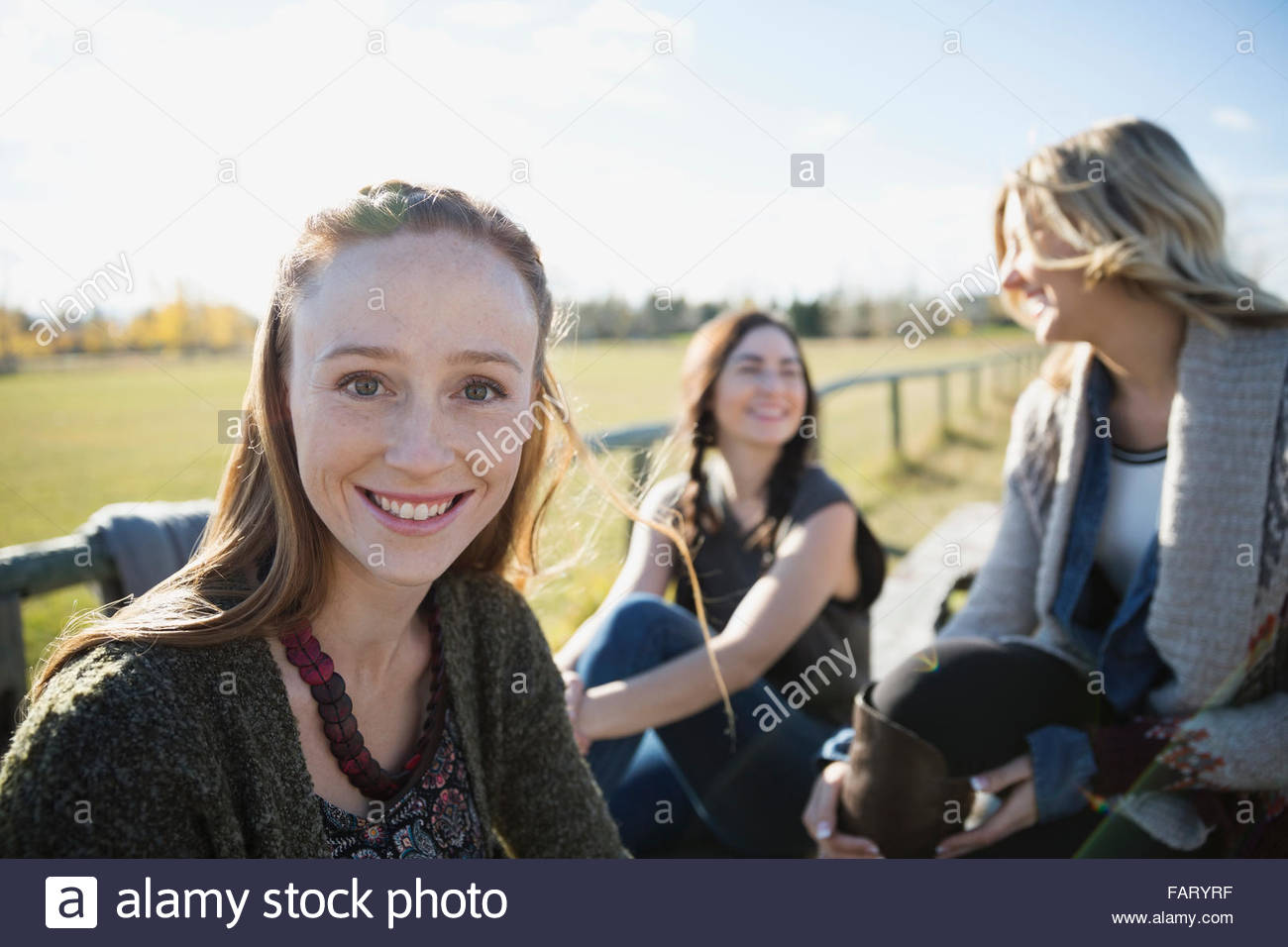 Portrait smiling young woman with friends in park - Stock Image