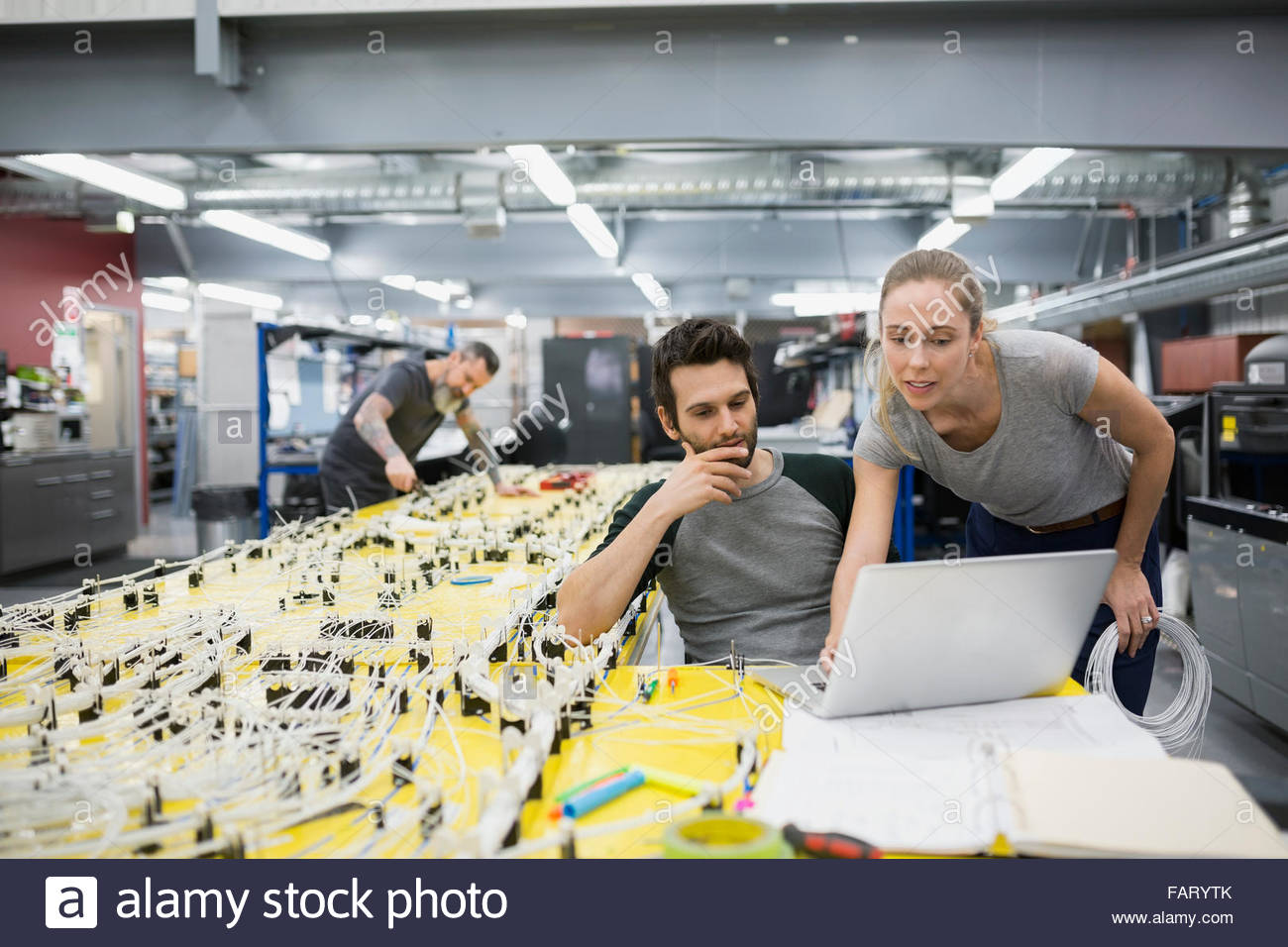 Helicopter technicians using laptop at wiring harness - Stock Image