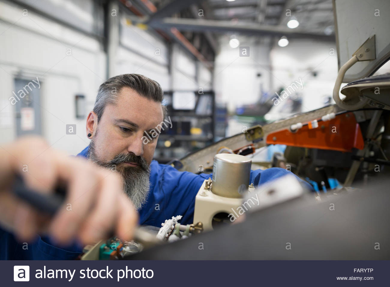 Helicopter mechanic repairing engine - Stock Image