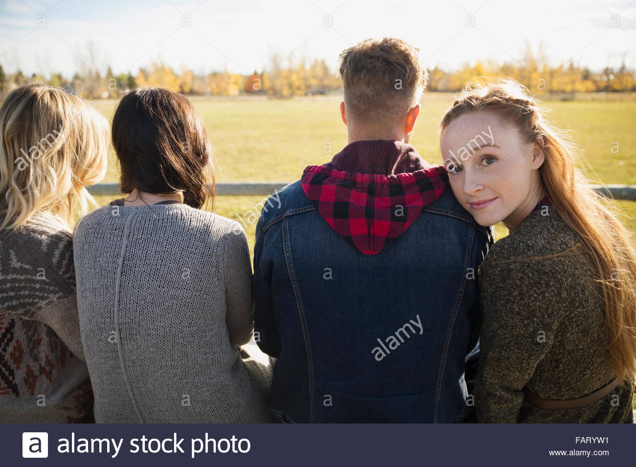 Portrait young woman with friends looking back in park Stock Photo