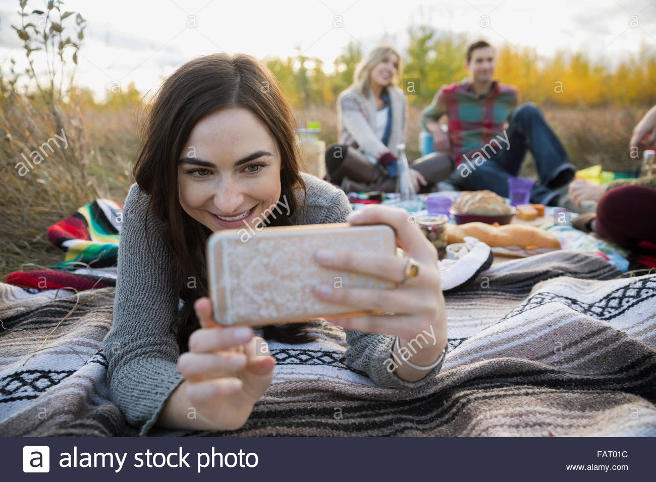Young woman taking selfie on picnic blanket in field - Stock Image