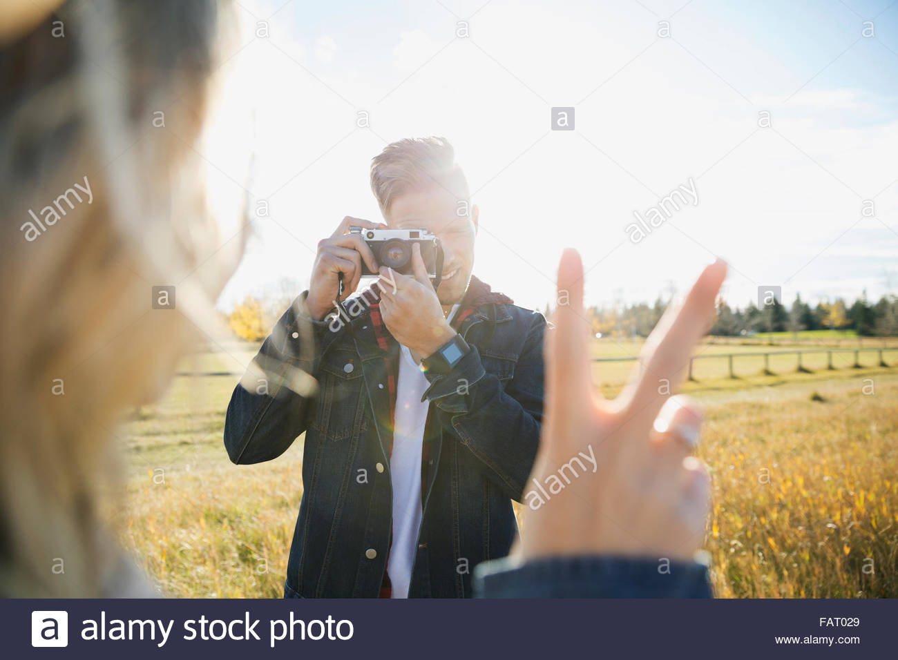 Young man photographing girlfriend gesturing peace sign - Stock Image