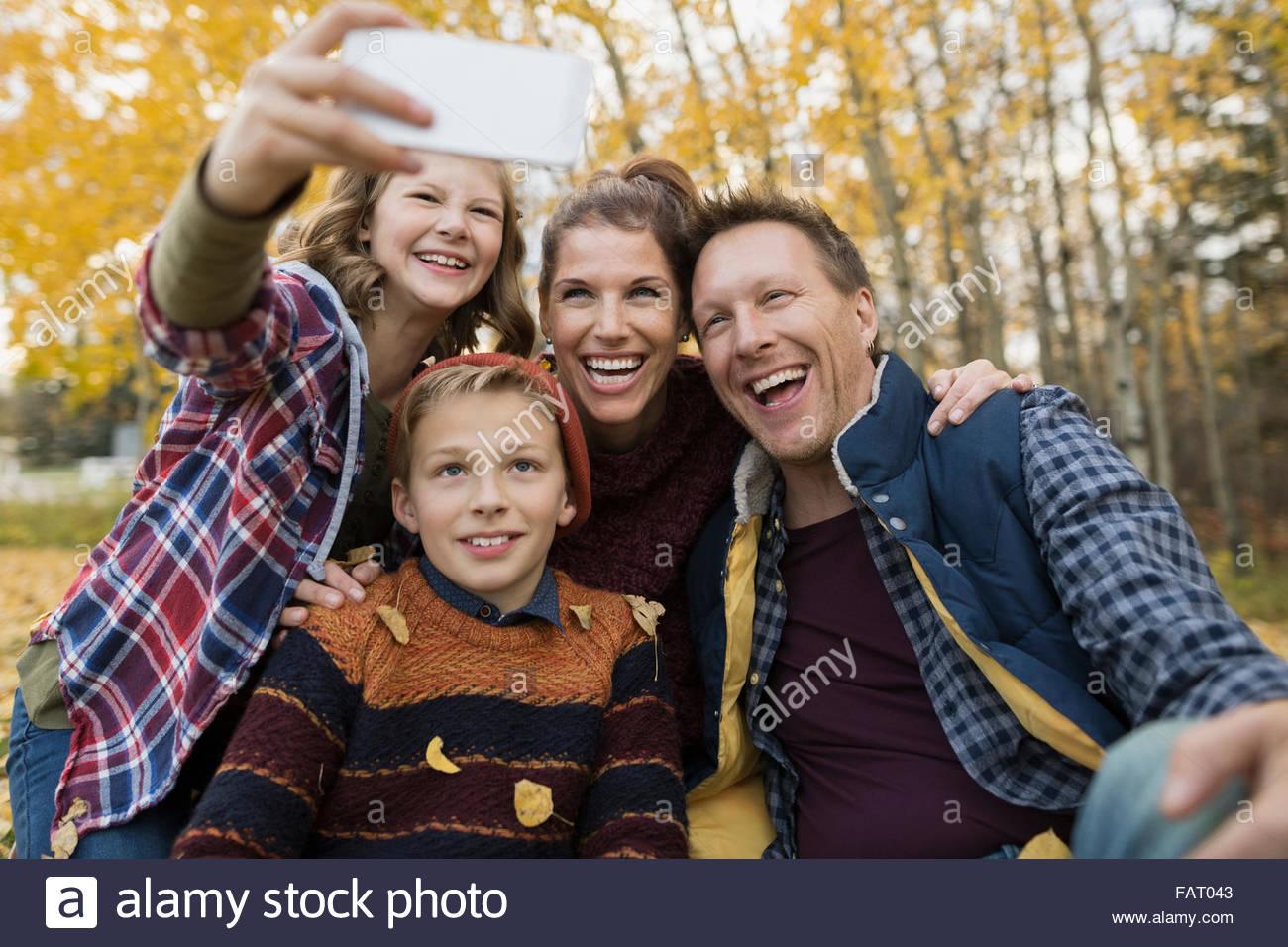Family taking selfie in autumn park - Stock Image