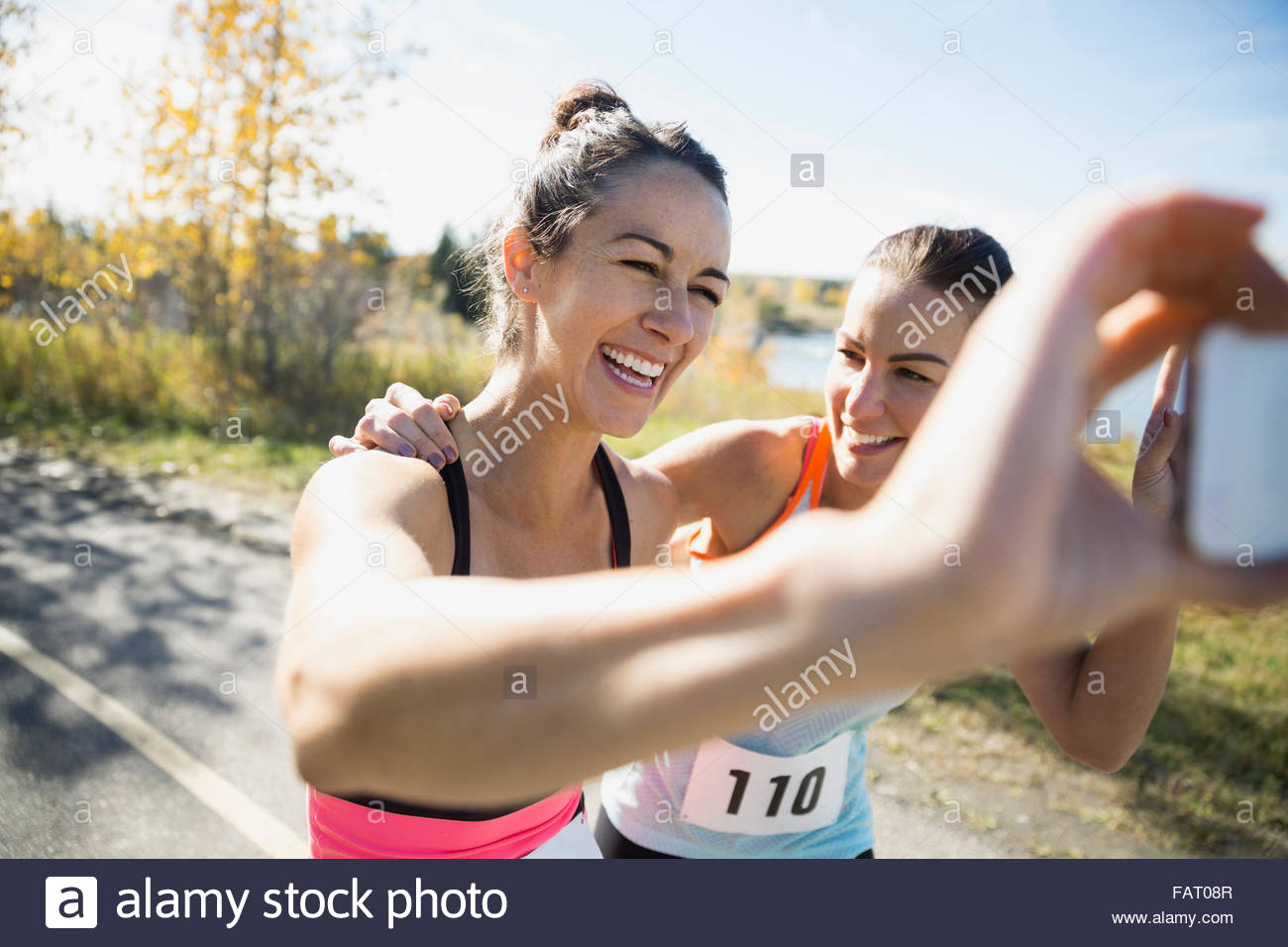 Laughing runners taking selfie on sunny path Stock Photo