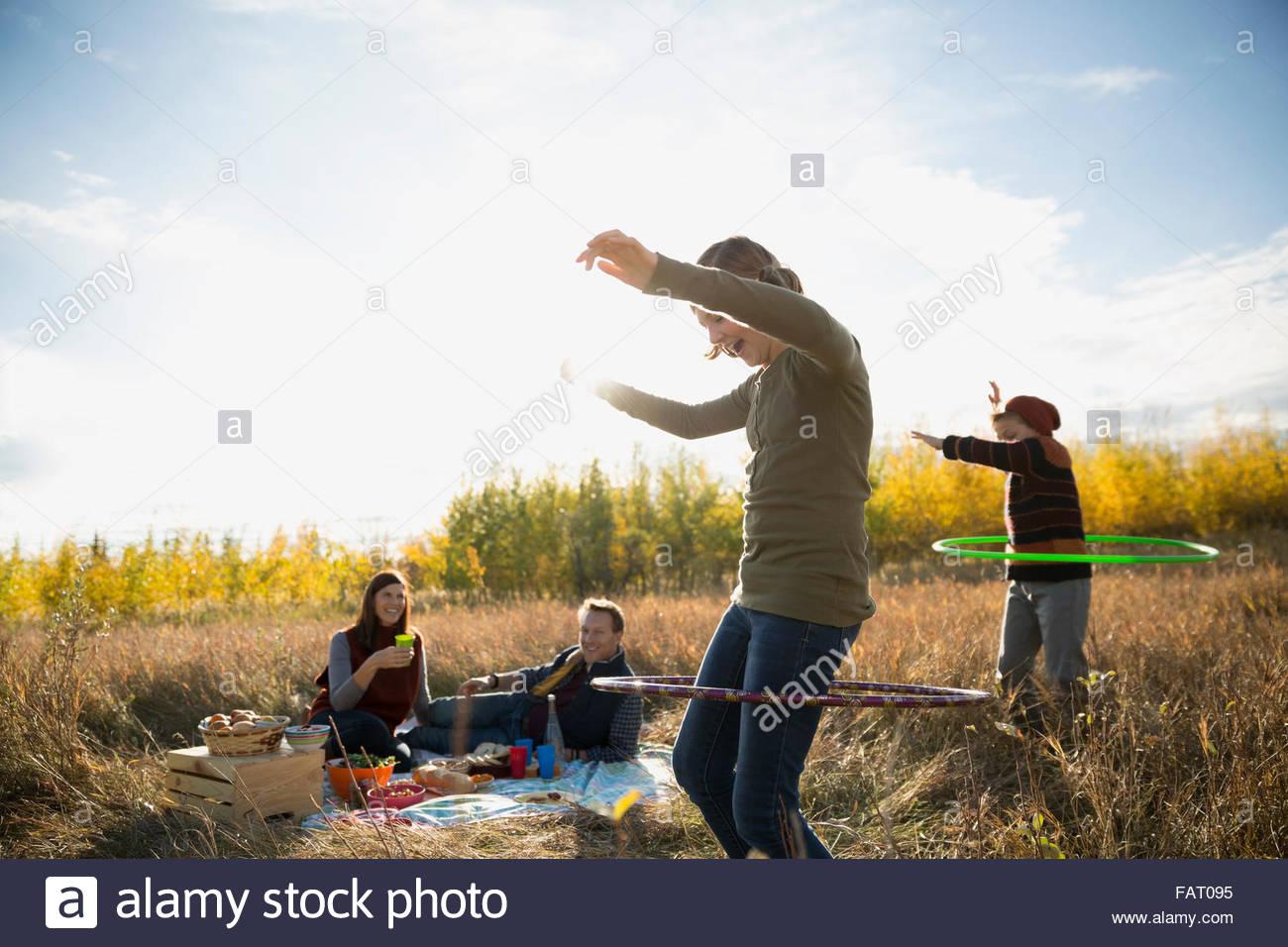 Family enjoying picnic spinning in plastic hoops - Stock Image
