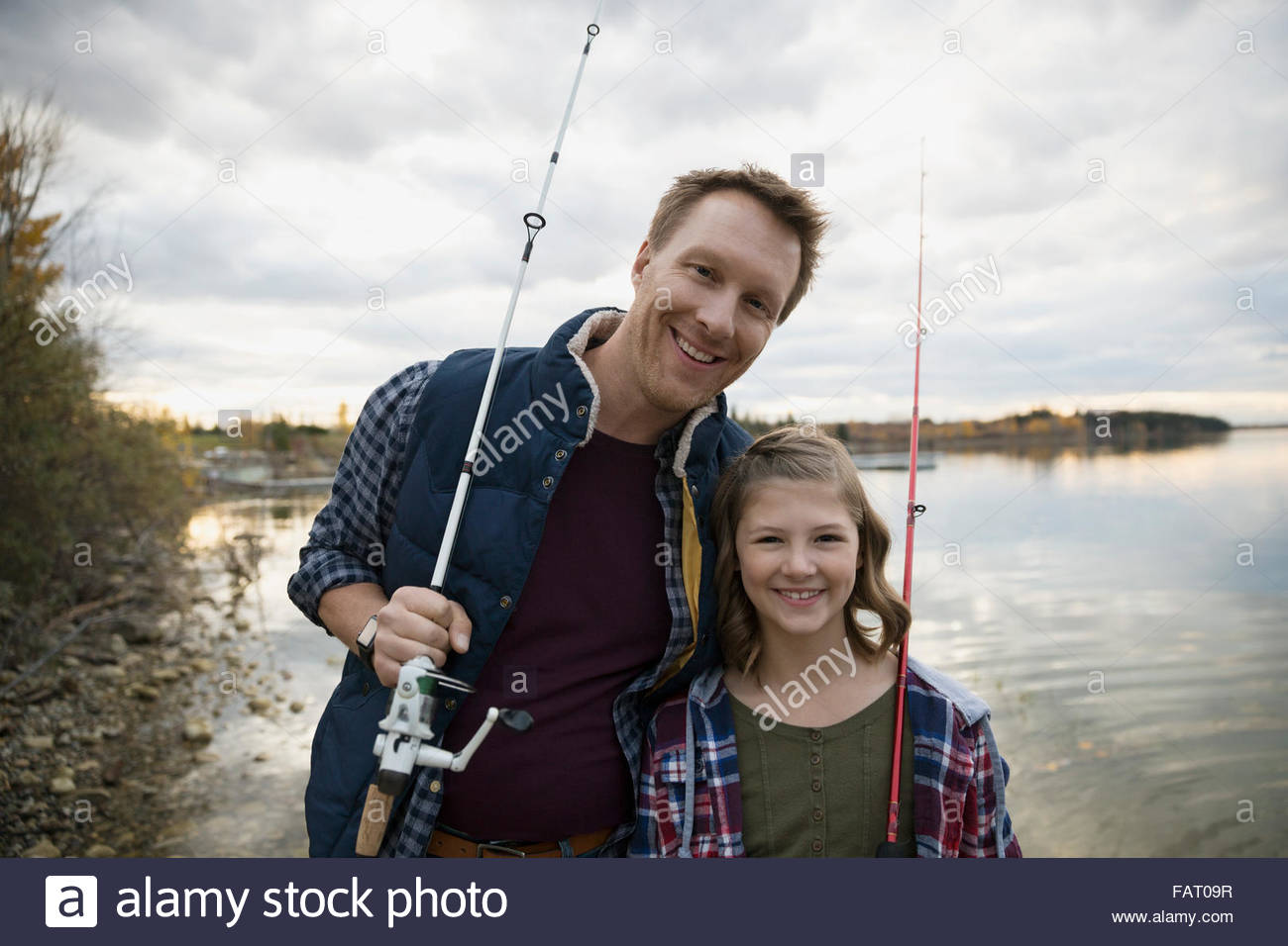 Portrait smiling father and daughter fishing rods lakeside - Stock Image