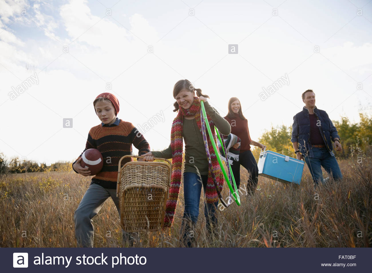 Family carrying picnic supplies in field - Stock Image