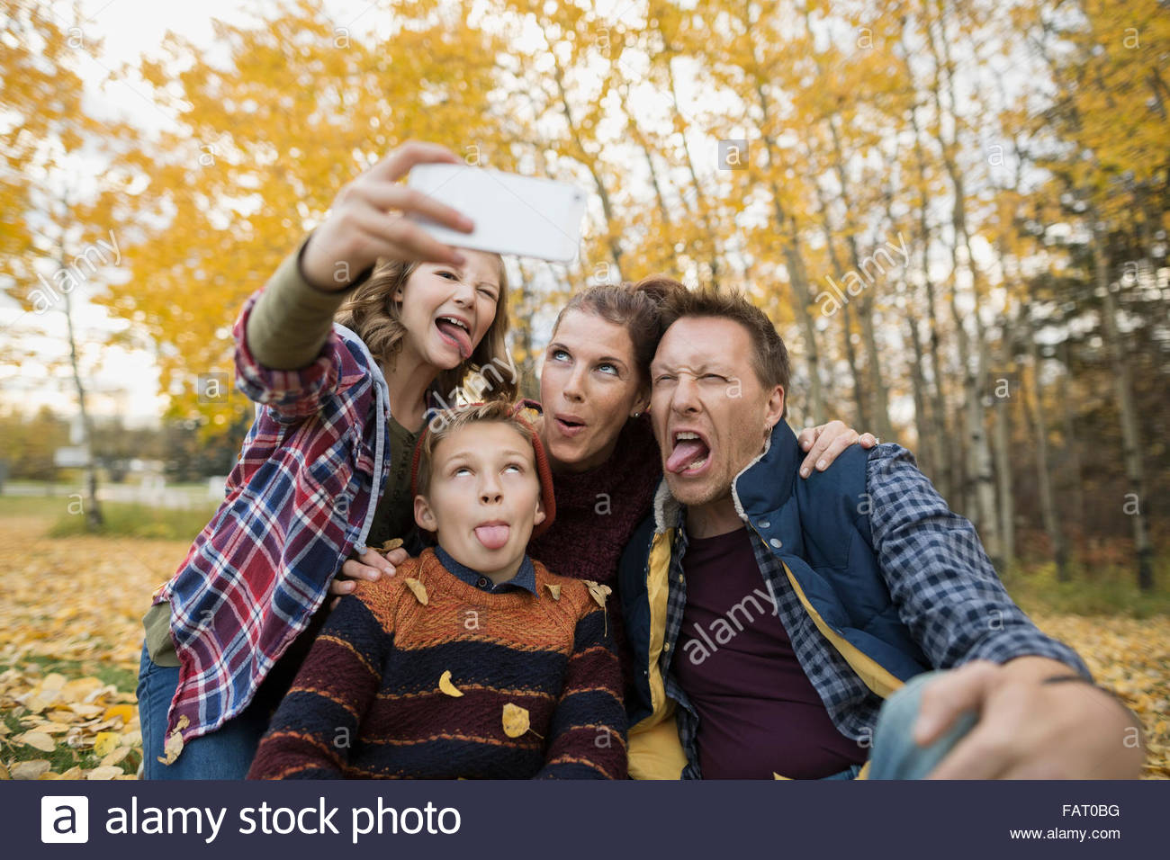 Silly family taking selfie making faces autumn park - Stock Image