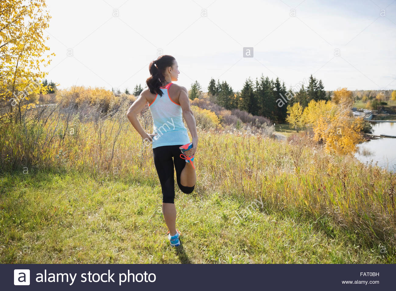 Jogger stretching leg in autumn field - Stock Image