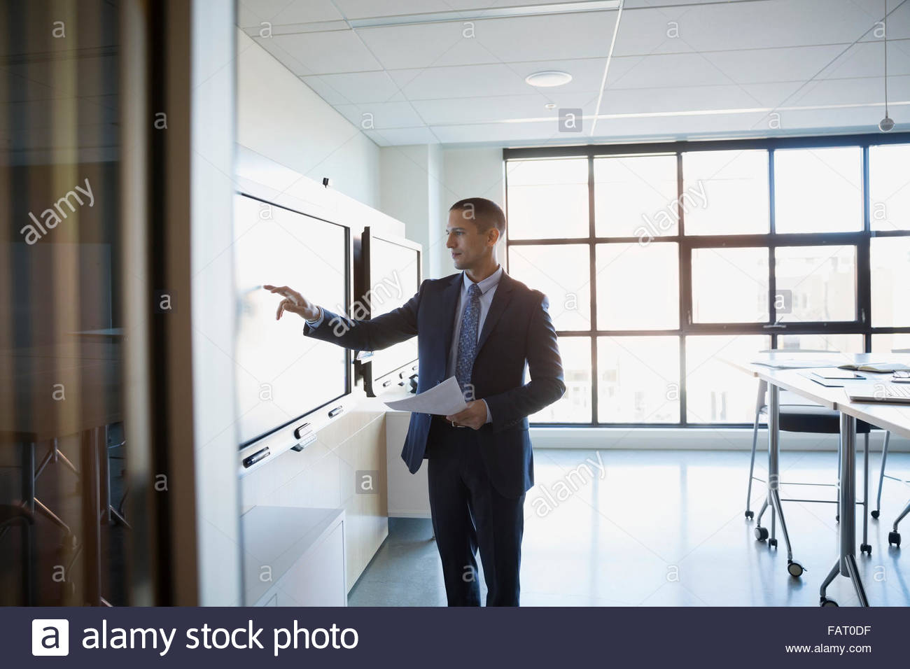 Businessman using touch screen in conference room - Stock Image