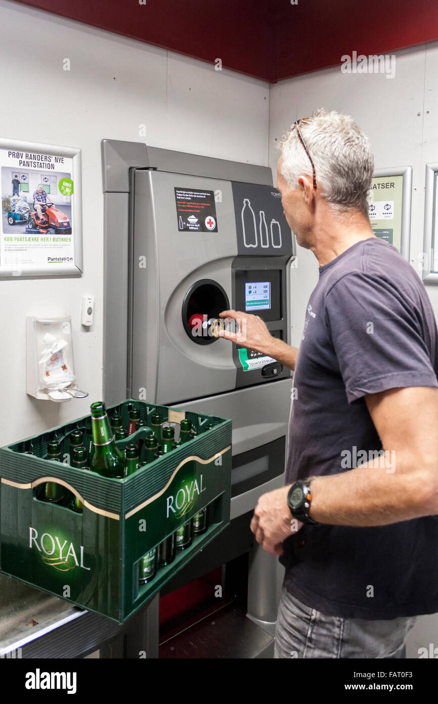 Man recycles bottles and cans in recycling machine in Danish supermarket. - Stock Image