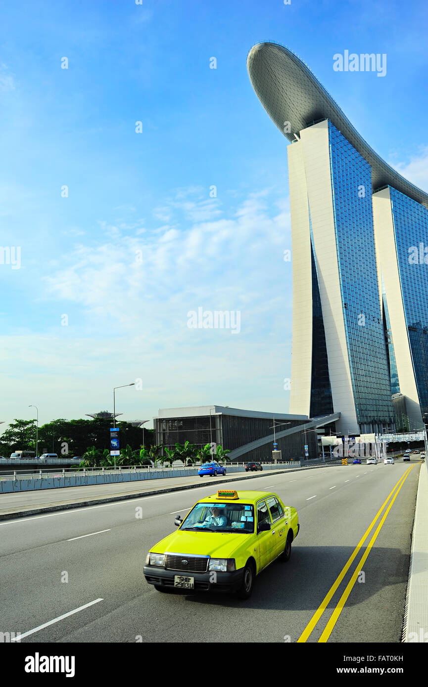 Taxi cab driving by the road in front of Marina Bay Sands hotel in Singapore. The government will spen Stock Photo