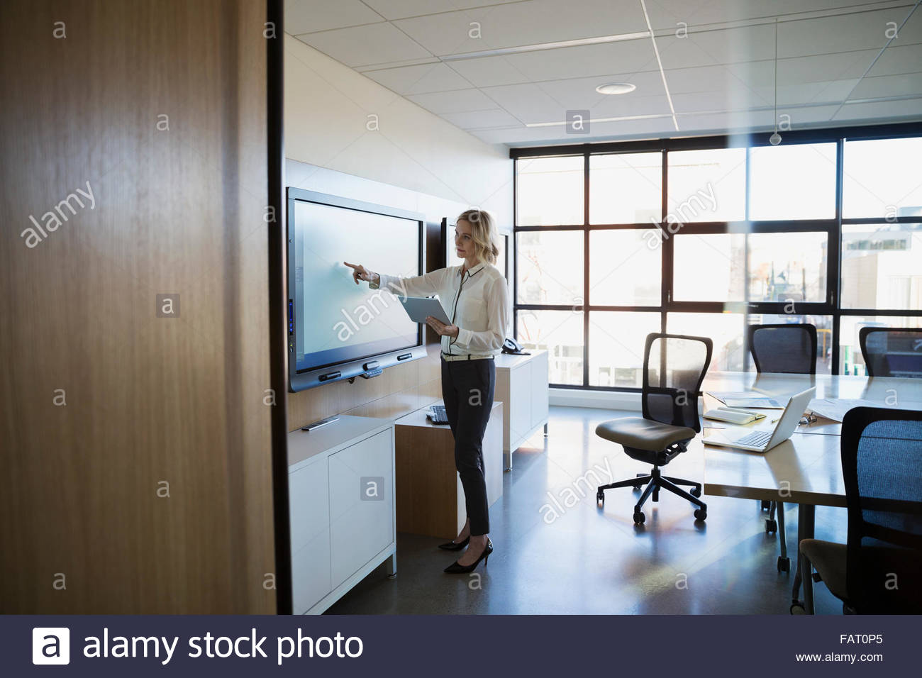 Businesswoman digital tablet using touch screen conference room - Stock Image