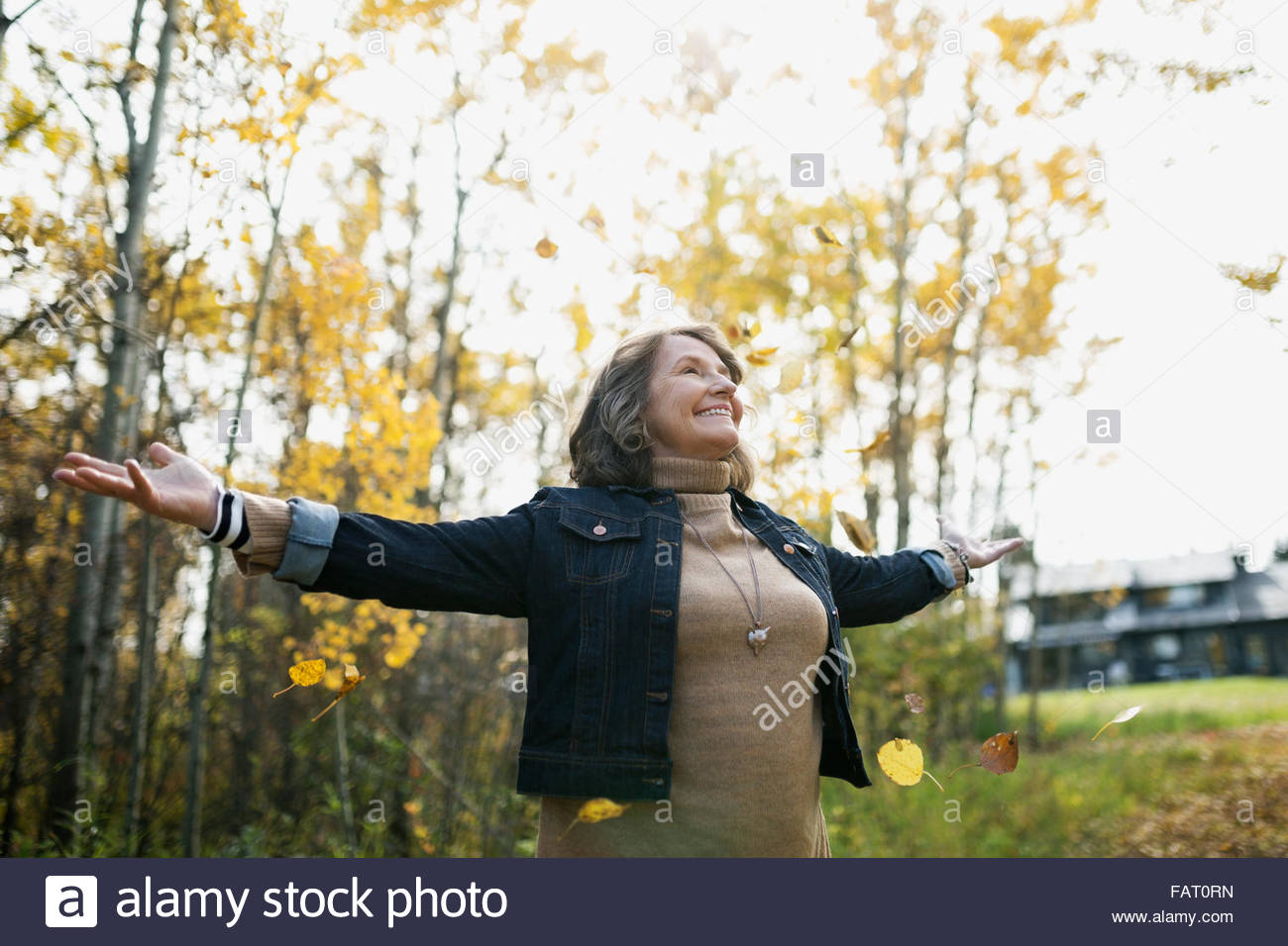 Autumn leaves falling around woman with arms outstretched - Stock Image