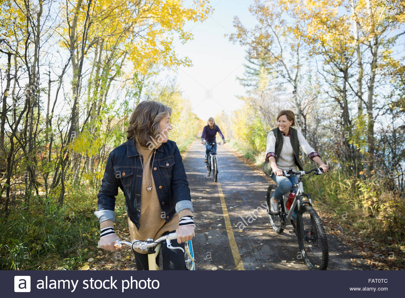 Friends bike riding on autumn path in park - Stock Image