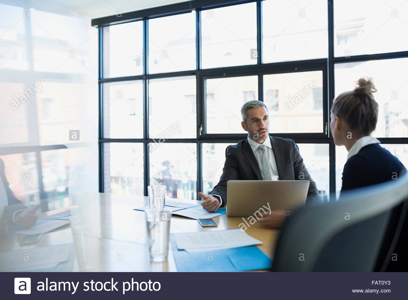 Business people talking at laptop in conference room - Stock Image