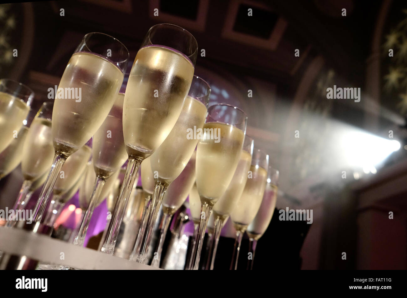 View from low down of some filled Champagne glasses at a party - Stock Image