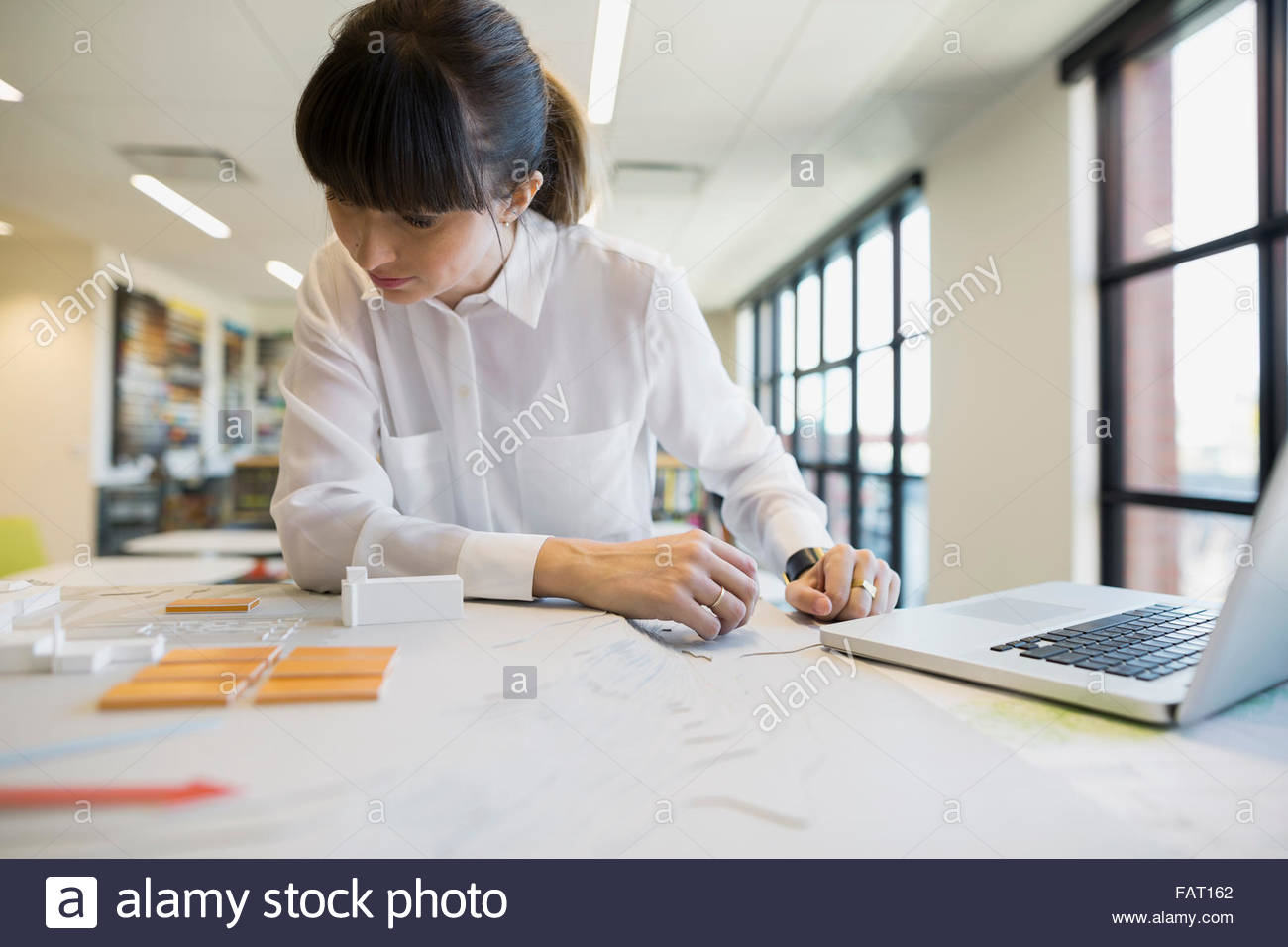 Focused architect examining models in office - Stock Image