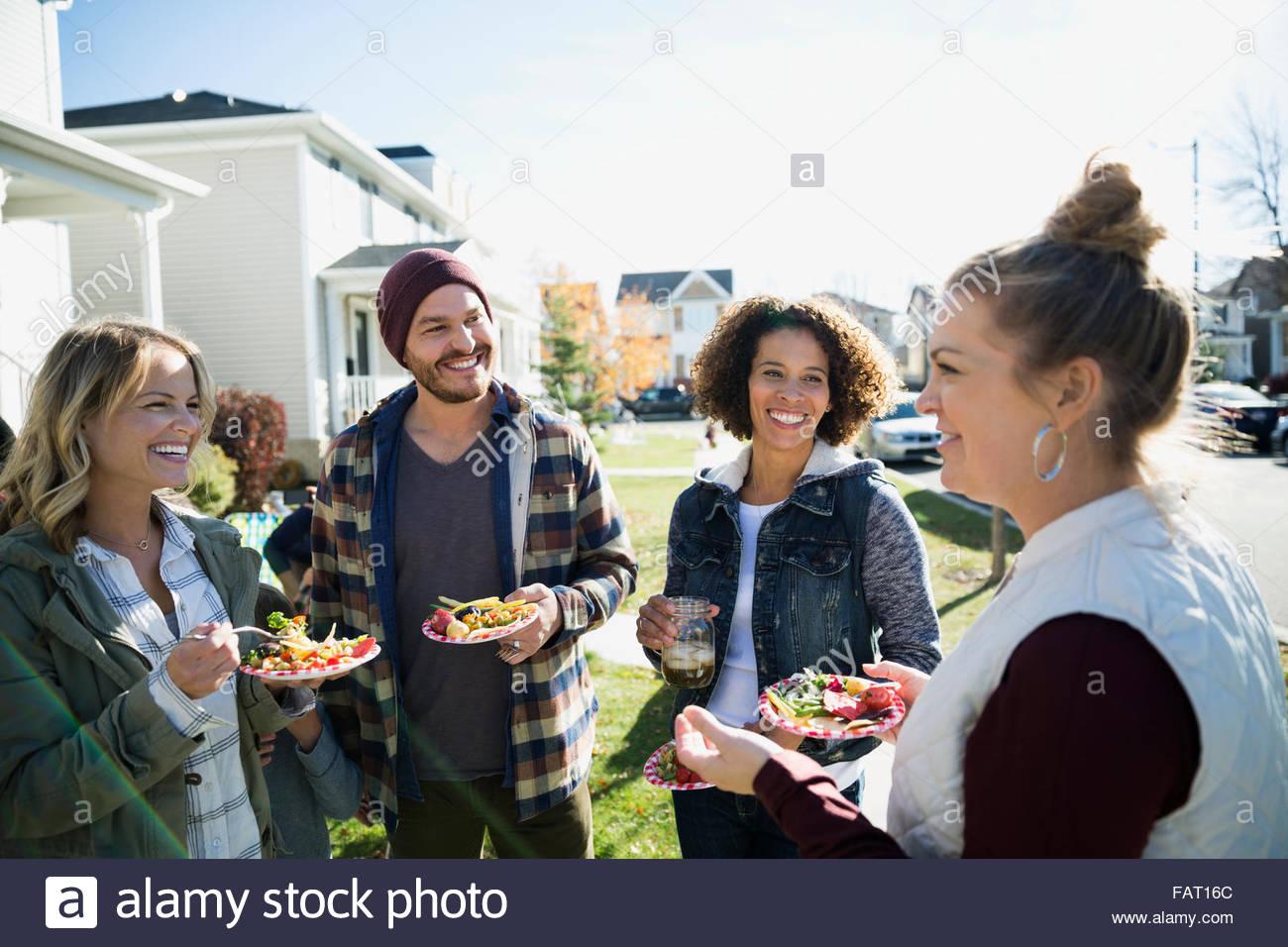 Neighbors enjoying potluck in front yard - Stock Image