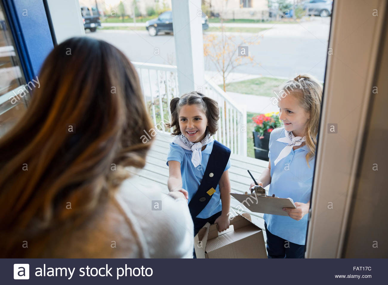 Girl scouts selling cookies woman at front door - Stock Image