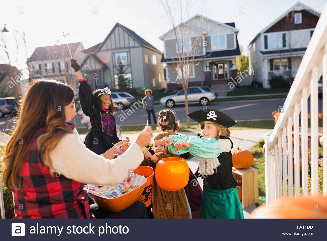 Woman with candy greeting Halloween trick or treaters - Stock Image