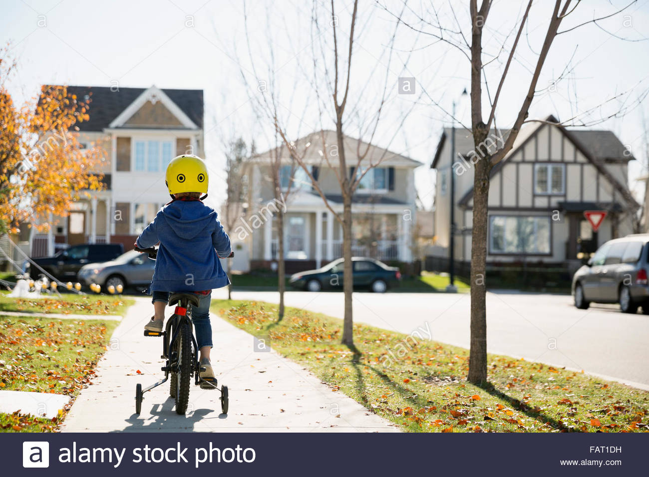 Rear view boy riding bike autumn neighborhood sidewalk - Stock Image