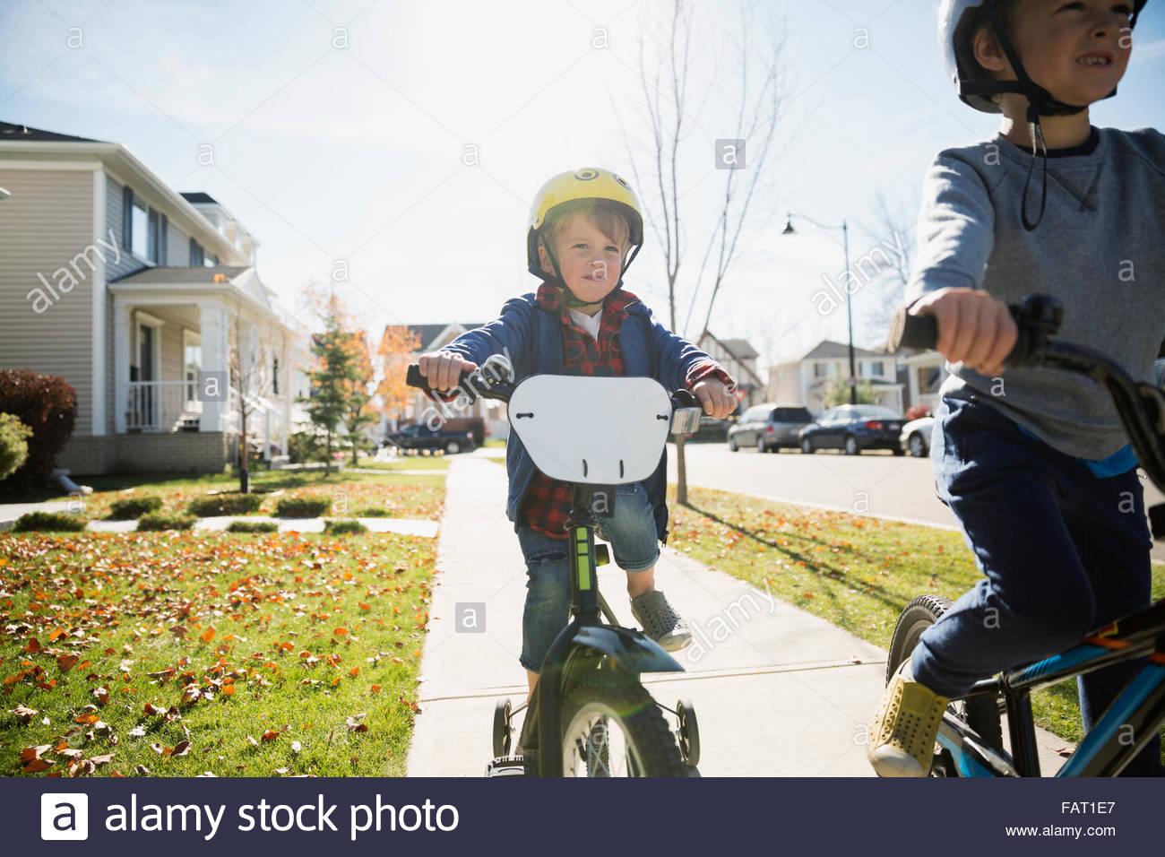 Boys riding bikes on autumn neighborhood sidewalk - Stock Image