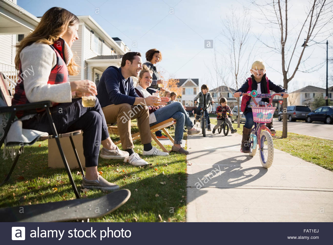Neighbors watching kids ride bikes on sidewalk - Stock Image