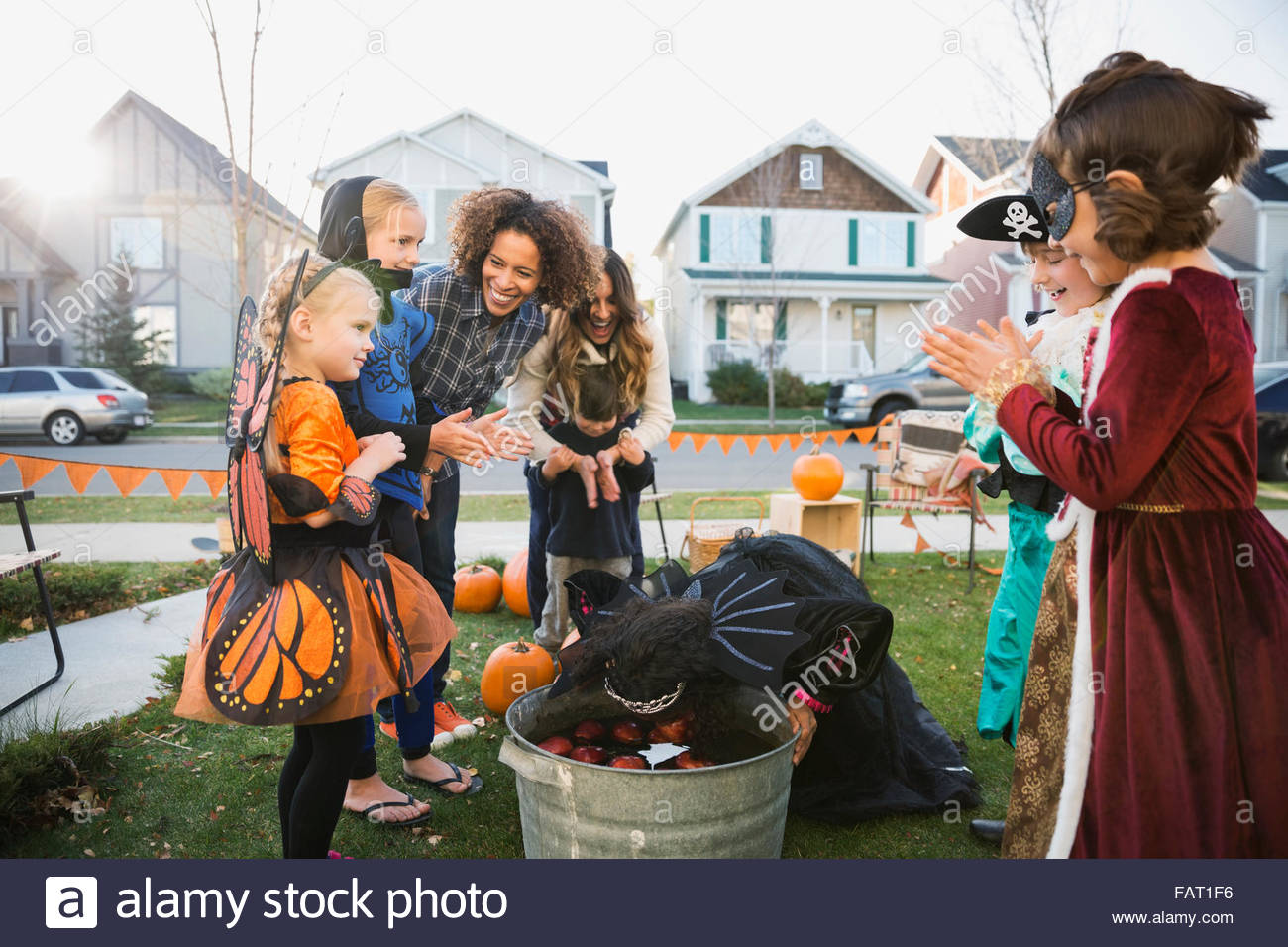 Kids in Halloween costumes bobbing for apples - Stock Image