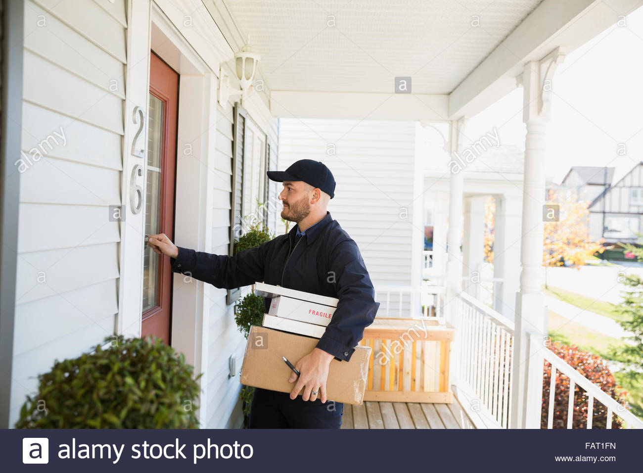 Delivery man with packages knocking at front door & Delivery man with packages knocking at front door Stock Photo ...