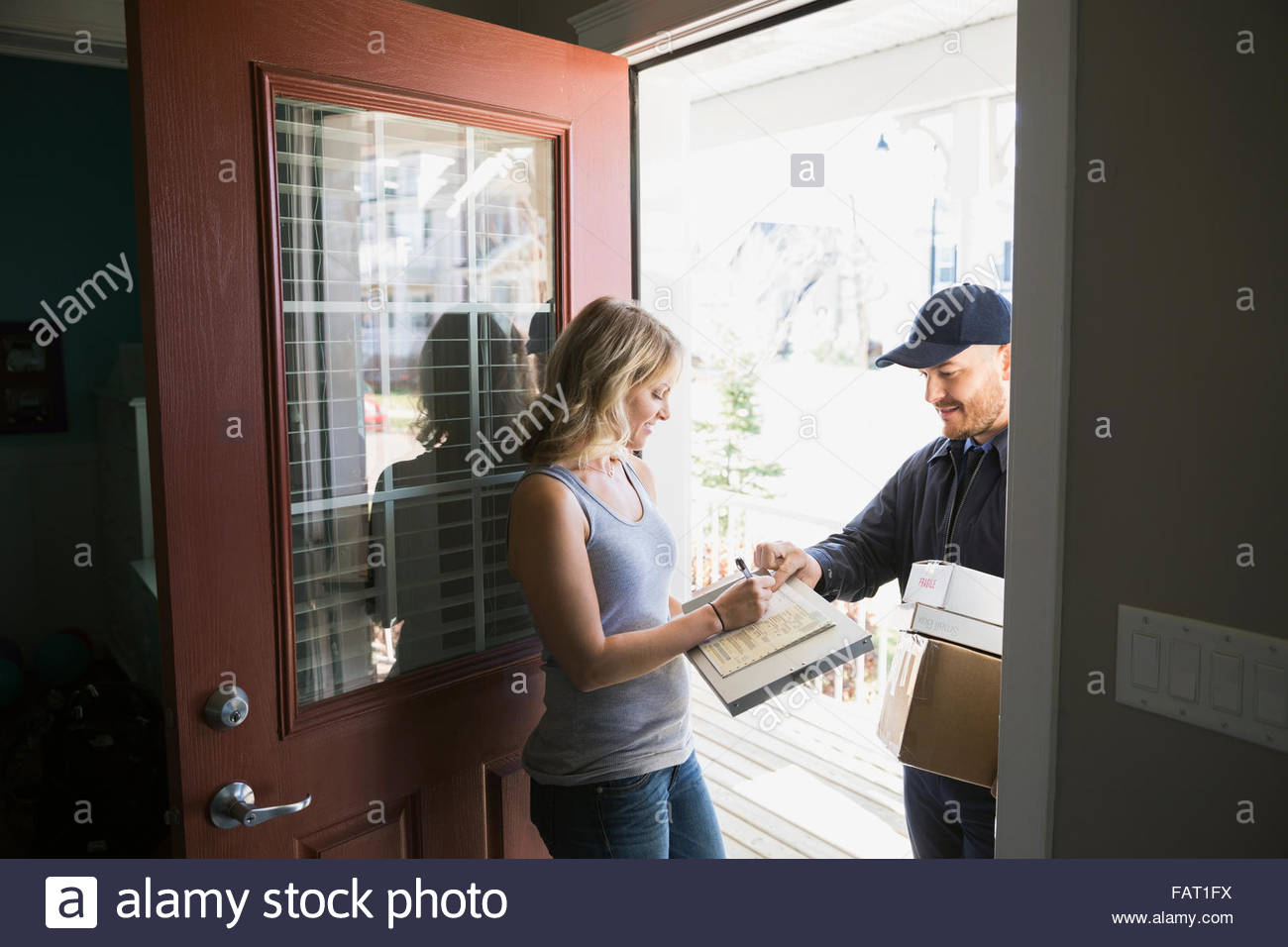 Woman signing for delivery at front door - Stock Image