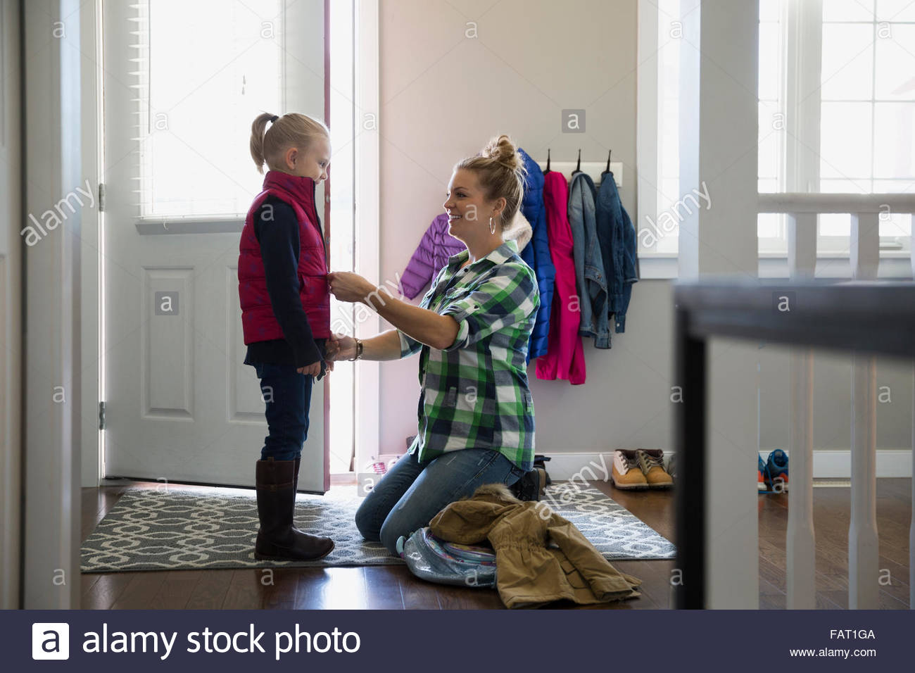 Mother zipping vest on daughter at front door - Stock Image