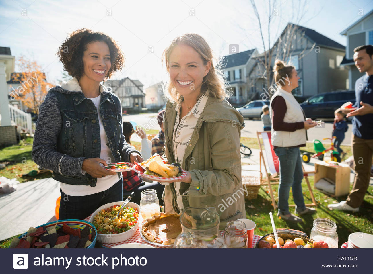 Portrait smiling neighbors enjoying potluck sunny front yard - Stock Image
