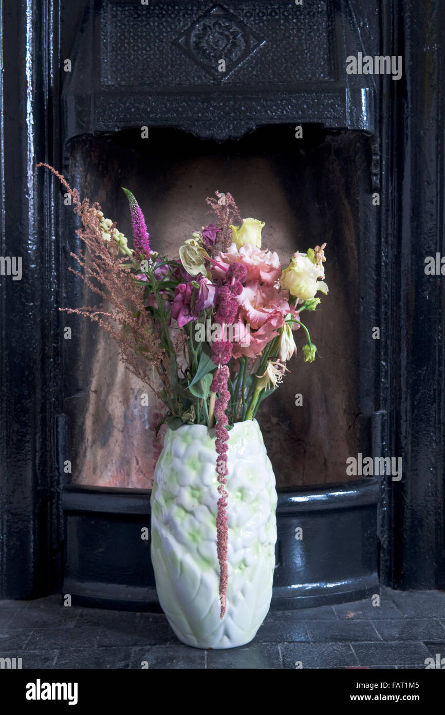 A vase of flowers sitting in front of a black cast iron fireplace - Stock Image