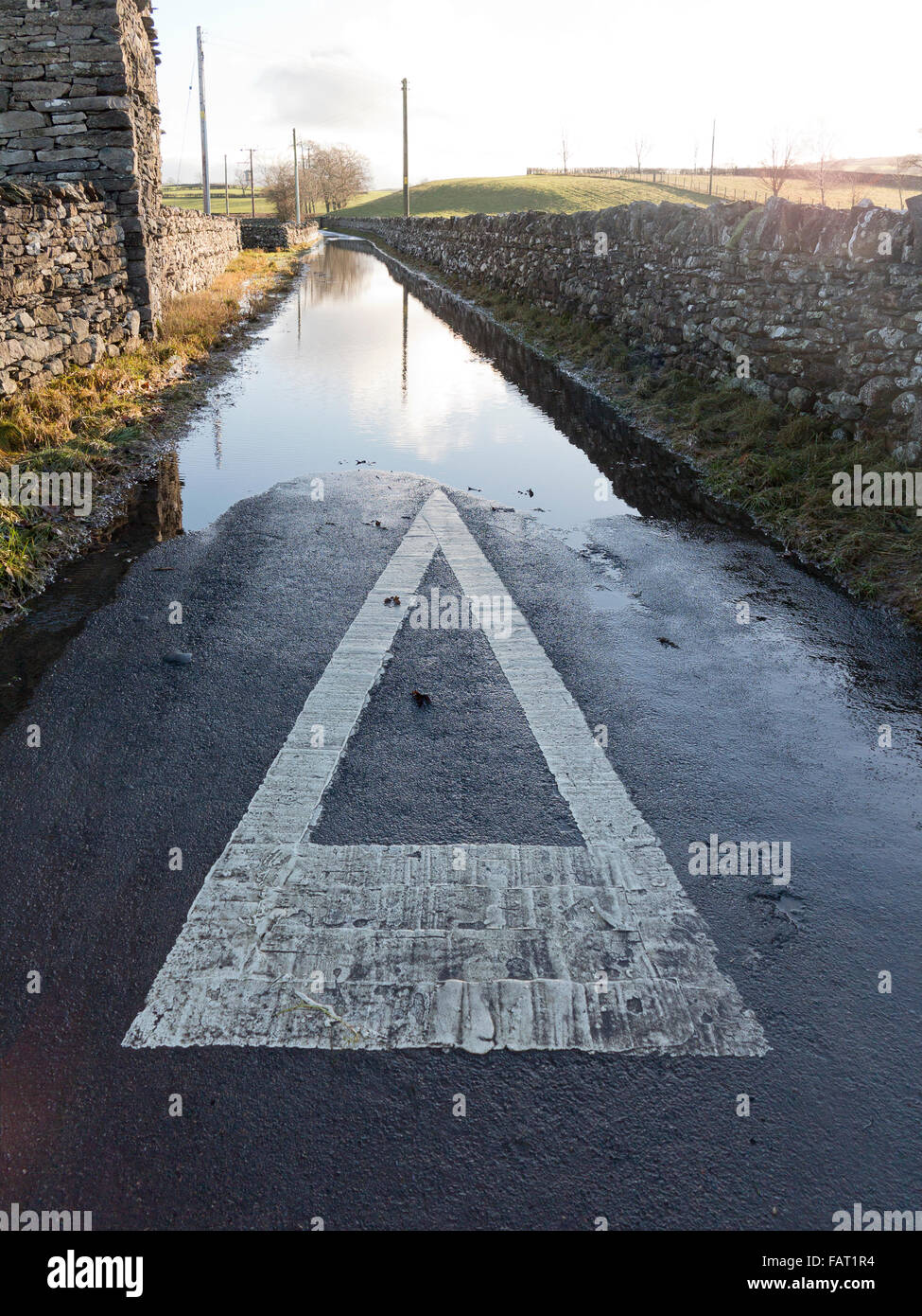 Looking down a partially flooded tarmac small road edged with drystone walls and showing directional triangle road - Stock Image
