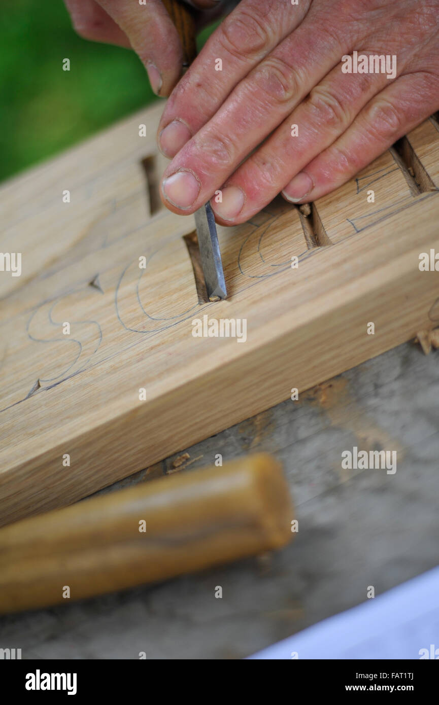 hands carving letters in wood with chisel