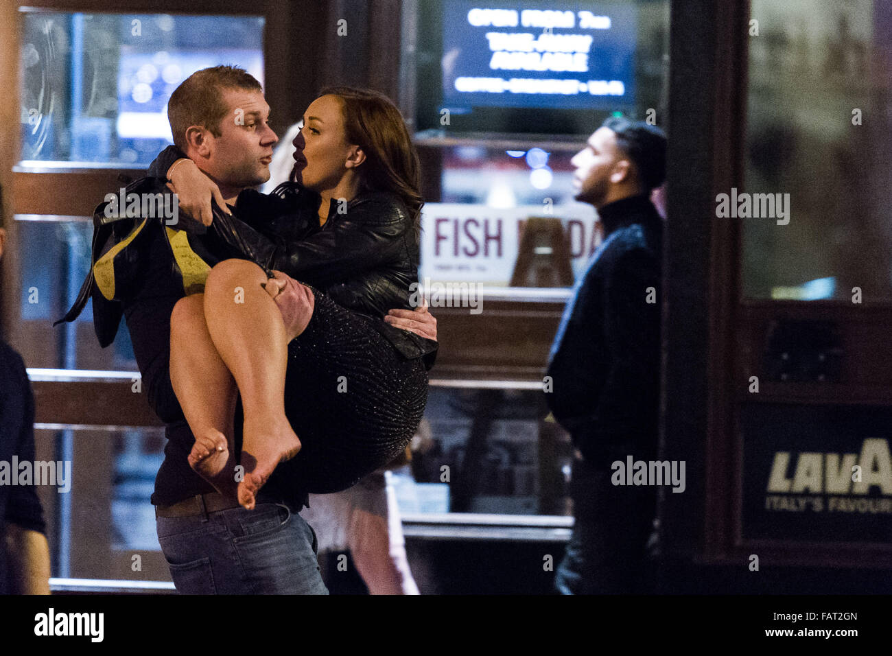 Pictured: A man carries a shoeless woman. Re: New Year's Eve in Cardiff, South Wales, UK. Early hours of Friday - Stock Image