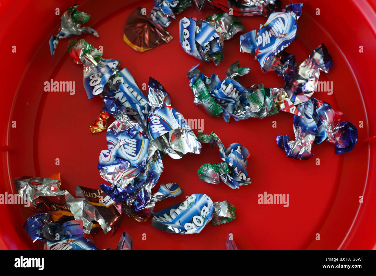 Wrappers left in the bottom of a tub of chocolate sweets. - Stock Image