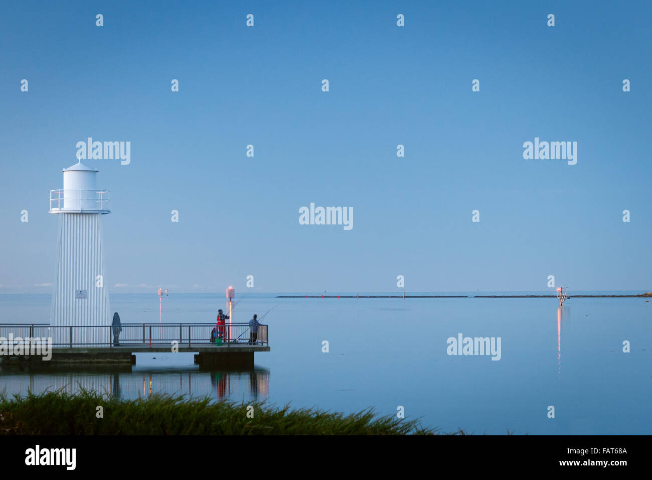 As the sun sets some locals fish near the mouth of the Mersey River in Devonport, Tasmania. - Stock Image