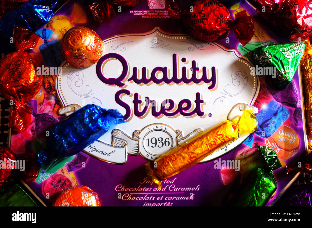 A Quality Street tin surrounded by chocolates in colourful wrappers. - Stock Image