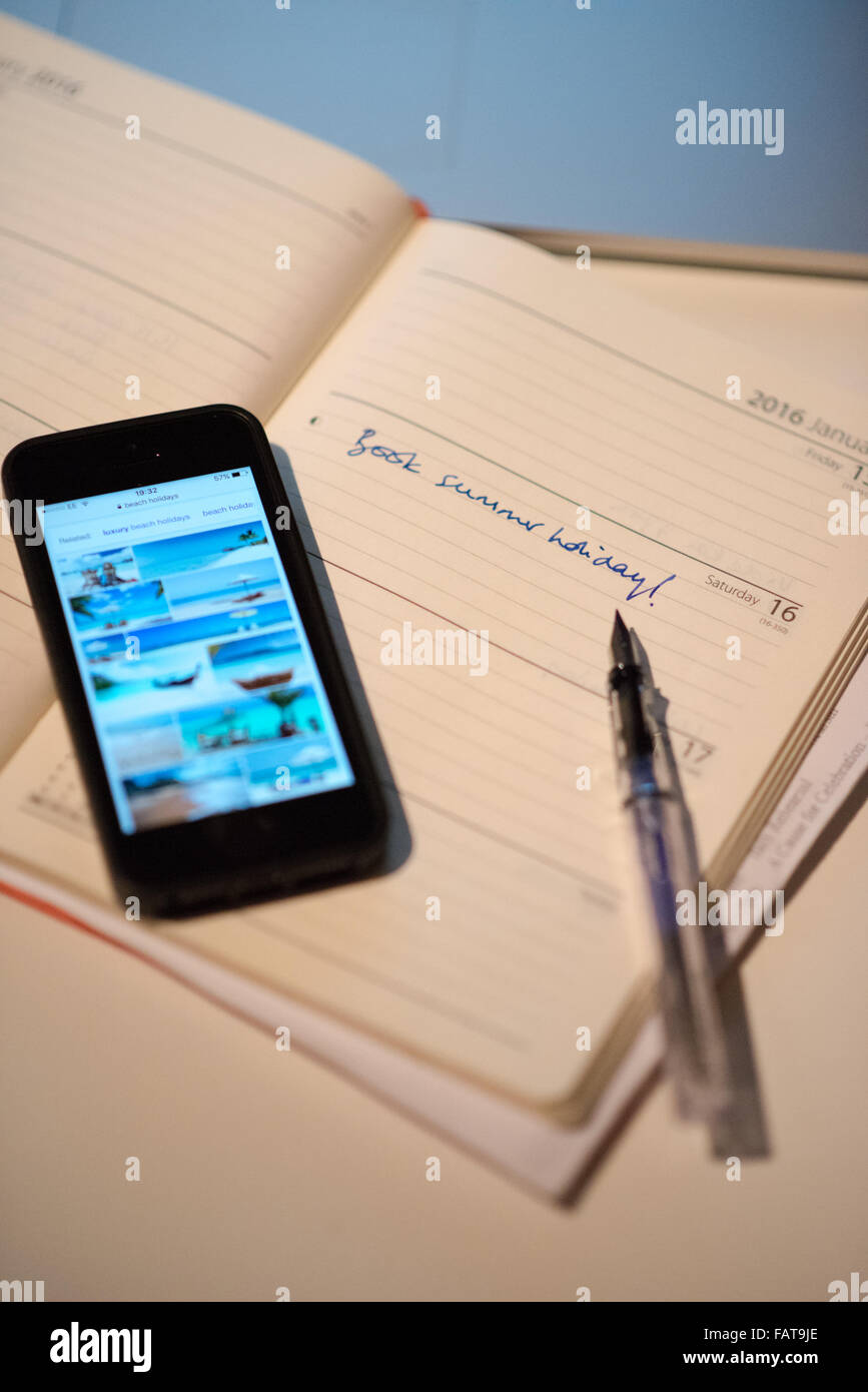An open diary with the words book summer holiday scribbled on a page alongside a smart phone with photos of package - Stock Image